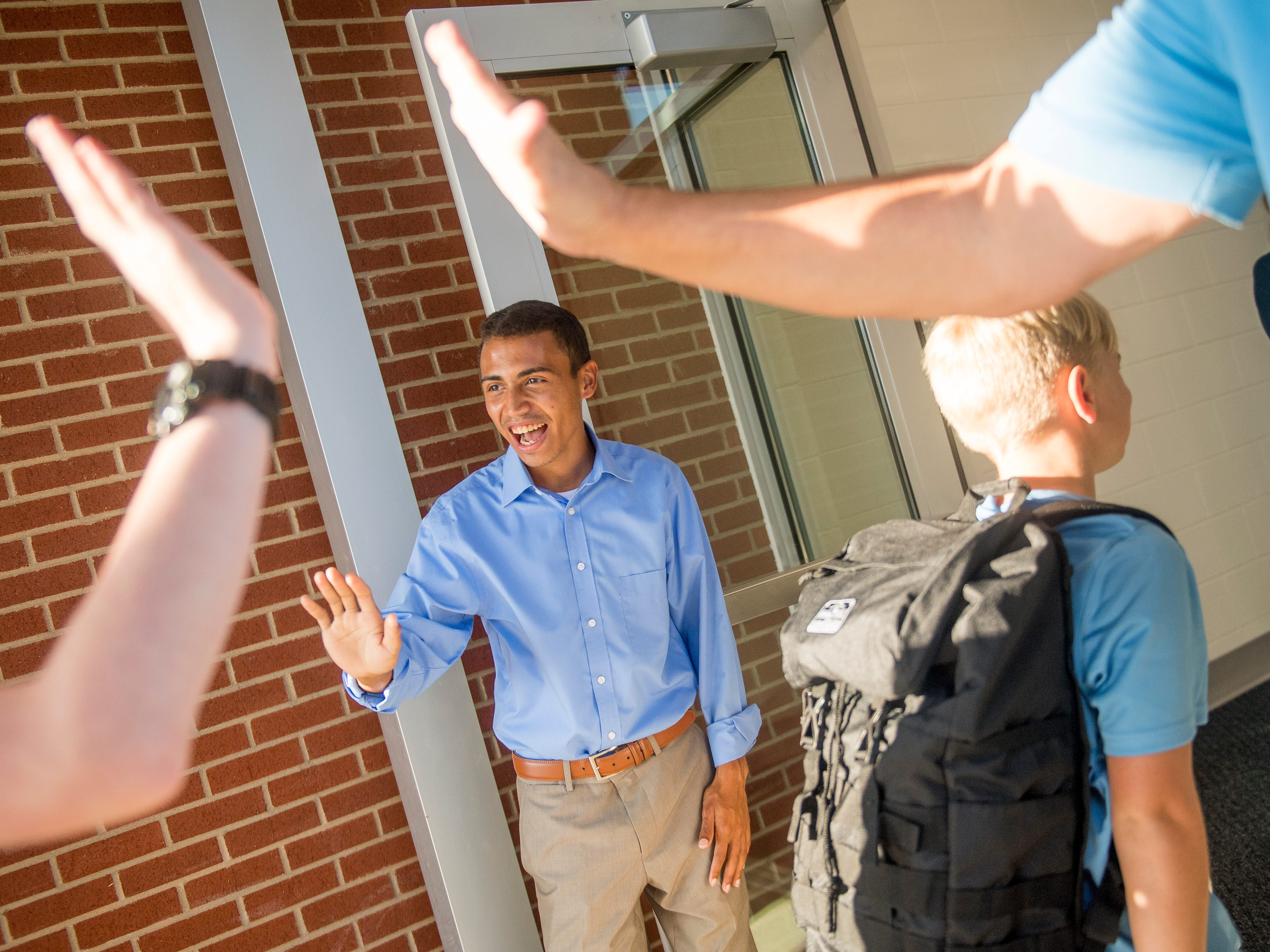 Seth Majors, center, smiles as he greets students with a high five as they step off the bus and enter the new Gibbs Middle School for the first day of school on Wednesday, August 8, 2018.