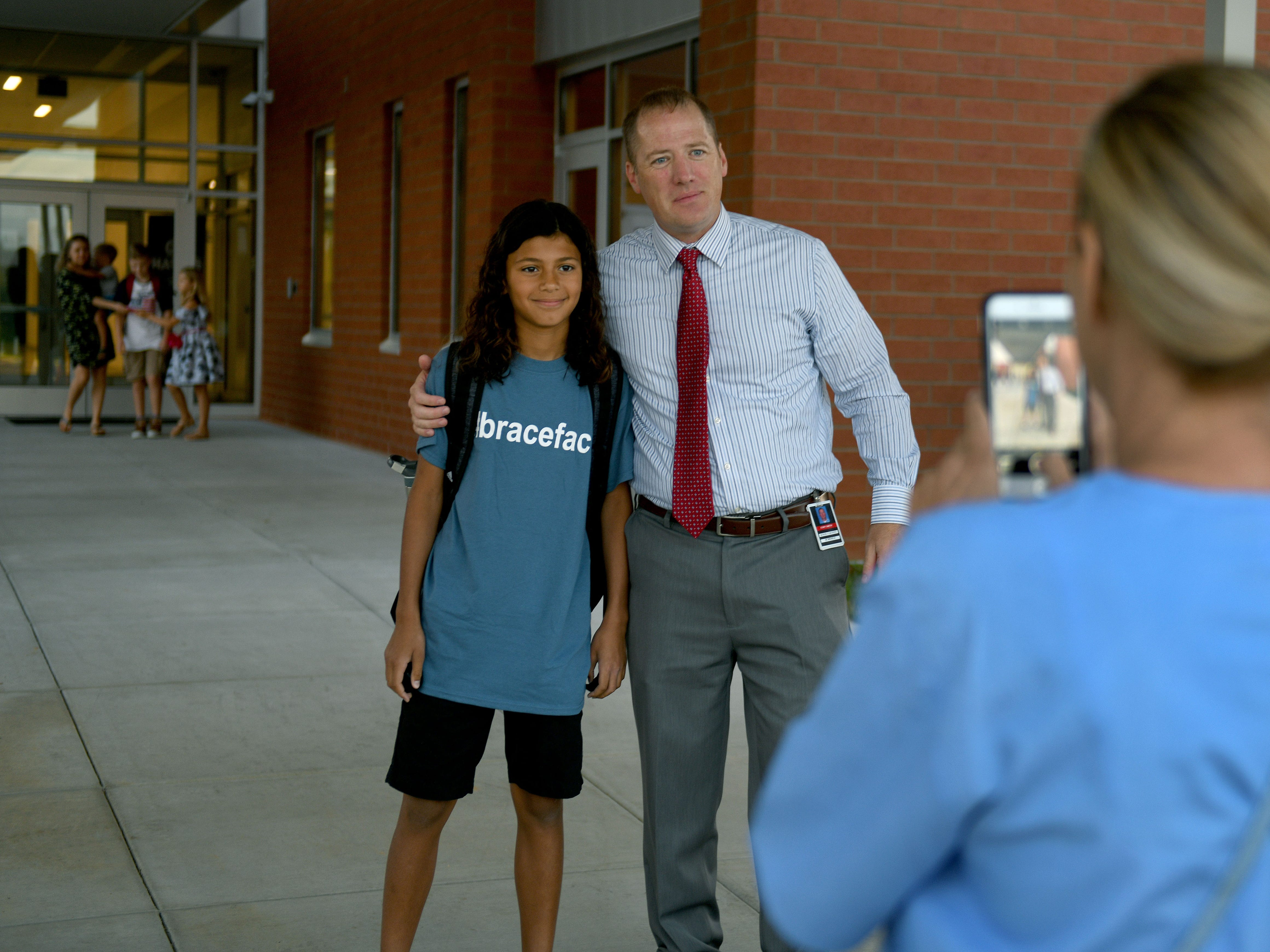 Hardin Valley Middle School Principal Cory Smith poses with Tristan Laanait, 11, while his mother Liz takes a photo at the entrance to the school Wednesday, August 8, 2018.  directed teachers and students to a smooth opening for the new school.
