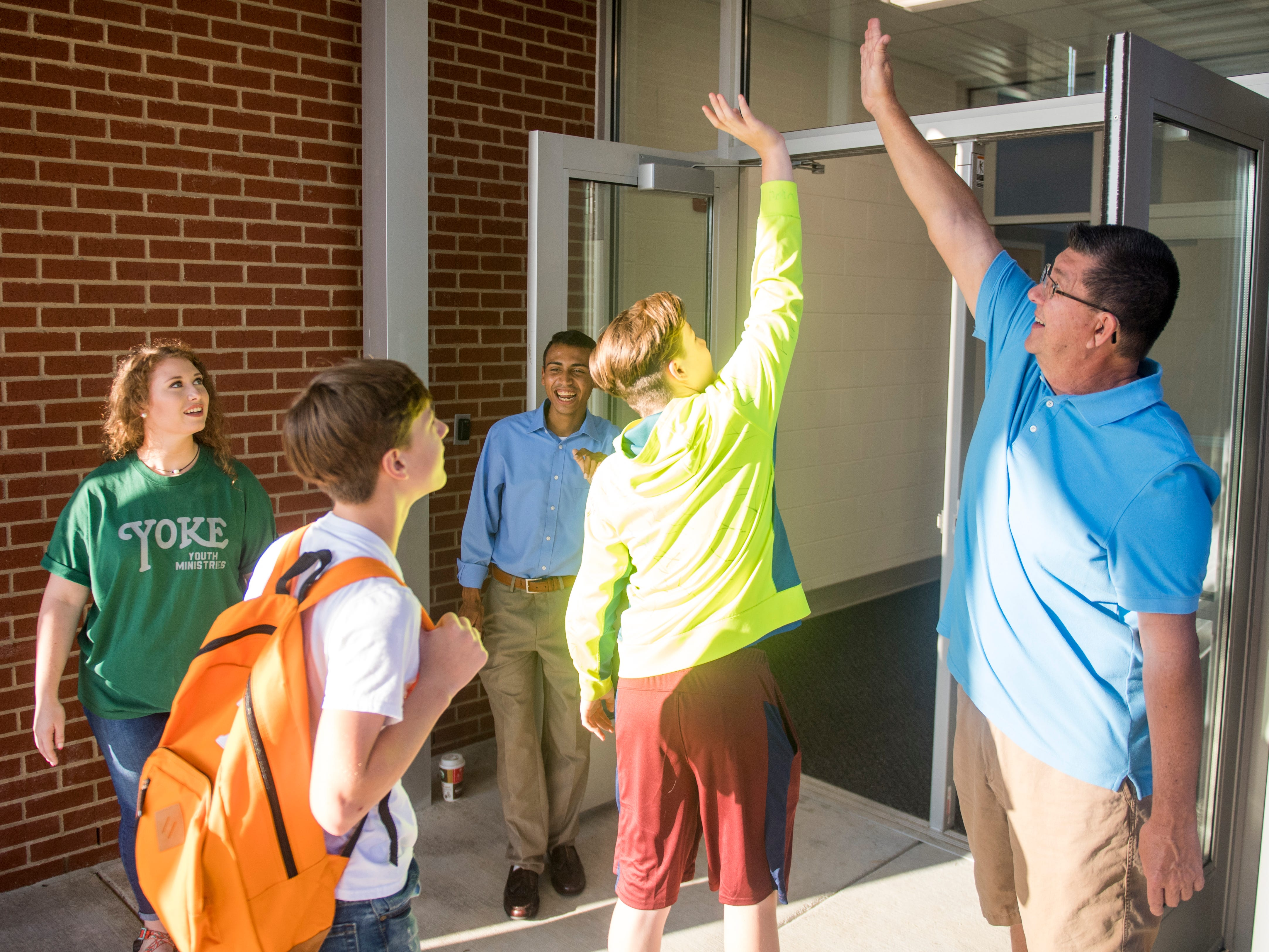 A student leaps to high five Fairview Baptist pastor Keith Weaver, right, as they enter the new Gibbs Middle School for the first day of school on Wednesday, August 8, 2018.