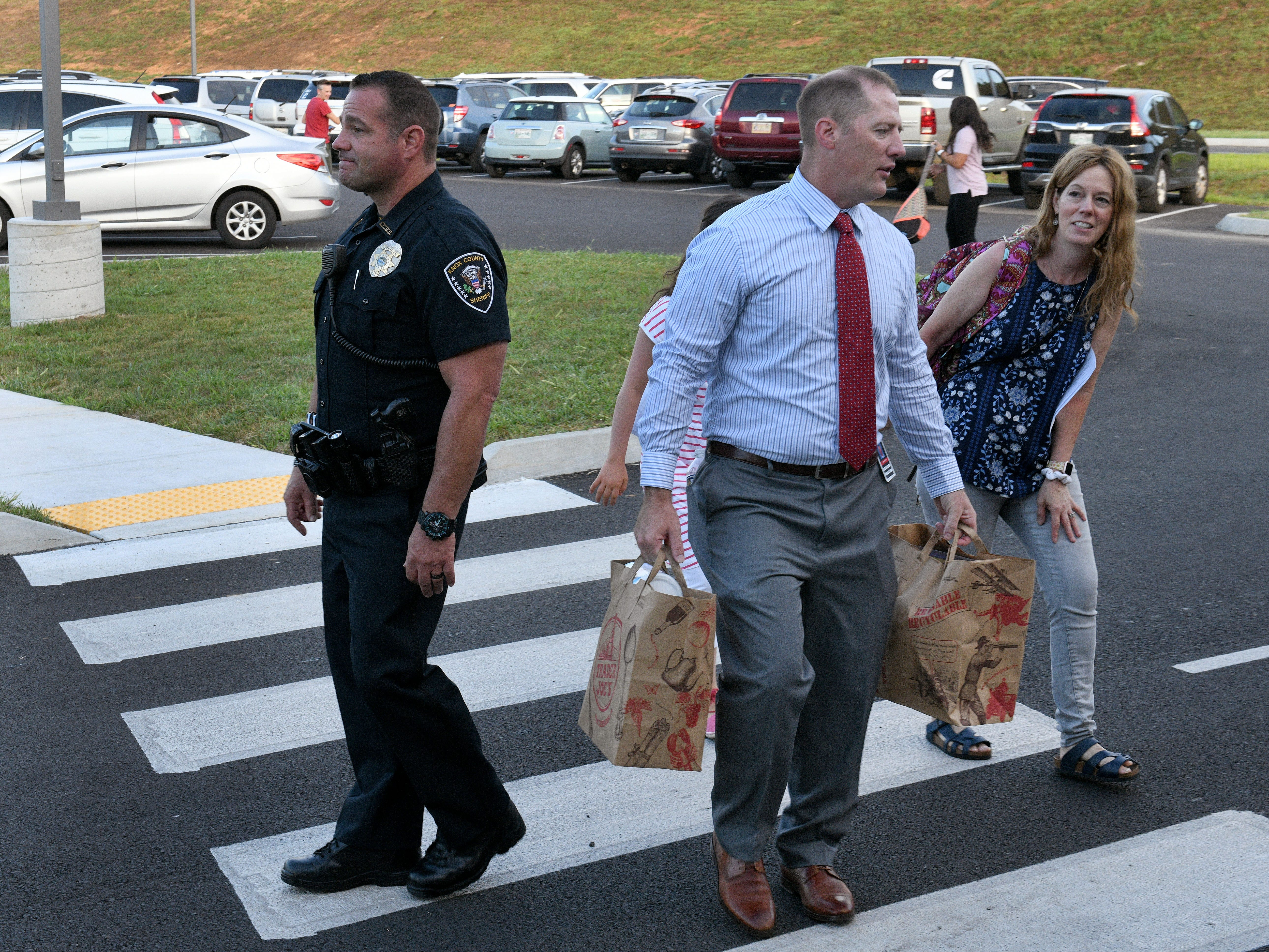 Hardin Valley Middle School Principal Cory Smith helps a student and her mother with packages while crossing the car rider line Wednesday, August 8, 2018.