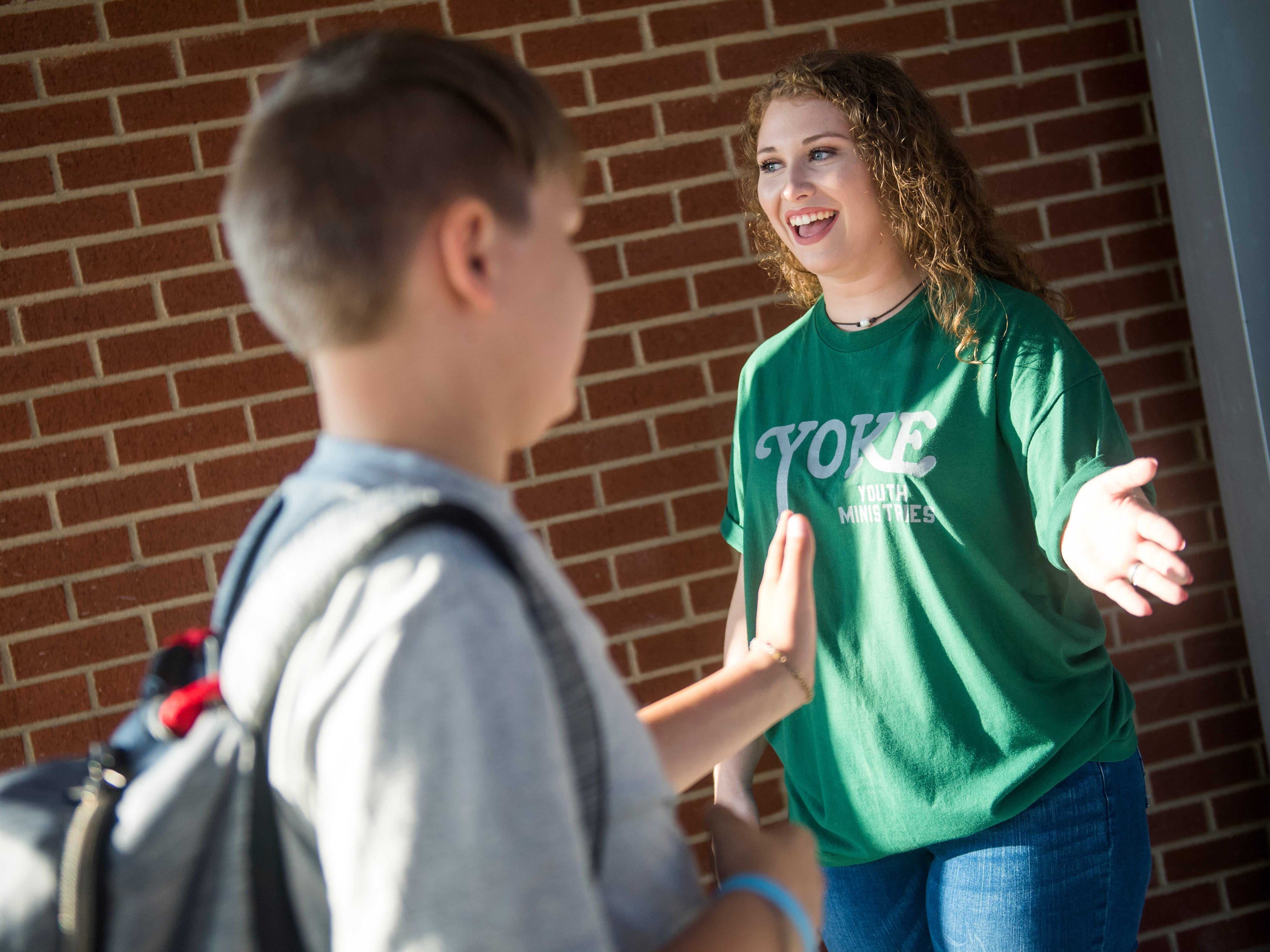 YOKE Youth Ministry's Sarah White, right, offers high fives to students as they enter the new Gibbs Middle School for the first day of school on Wednesday, August 8, 2018.