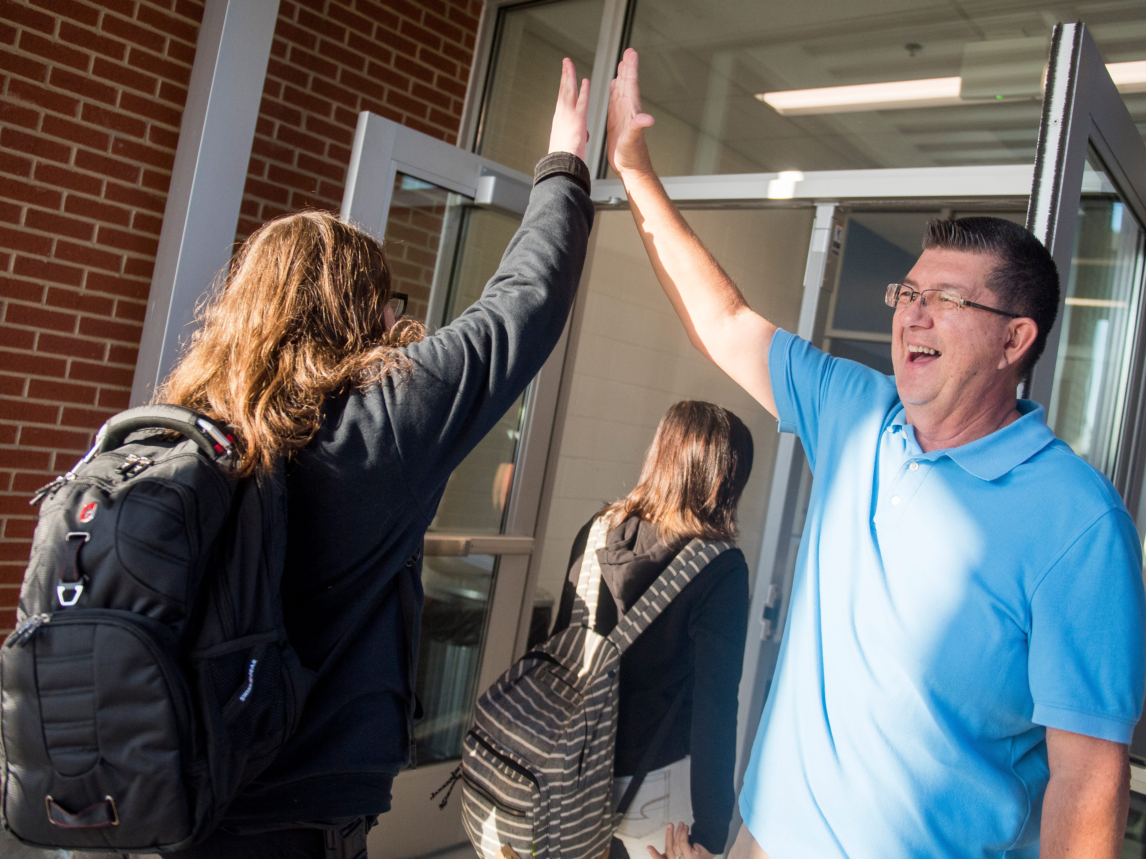 Fairview Baptist pastor Keith Weaver, right, high fives students as they enter the new Gibbs Middle School for the first day of school on Wednesday, August 8, 2018.