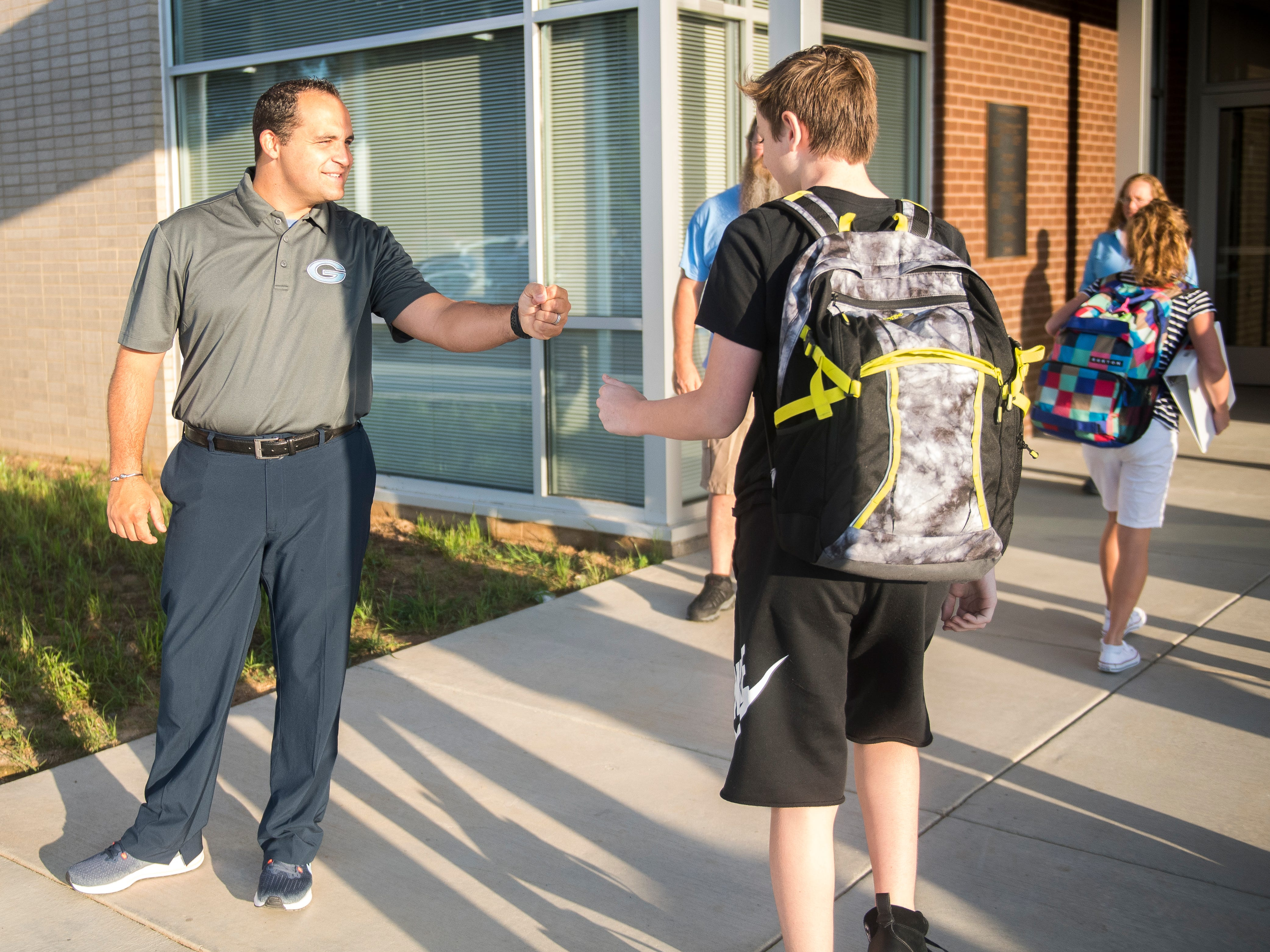 Students get high fives and handshakes as they enter the new Gibbs Middle School for the first day of school on Wednesday, August 8, 2018.