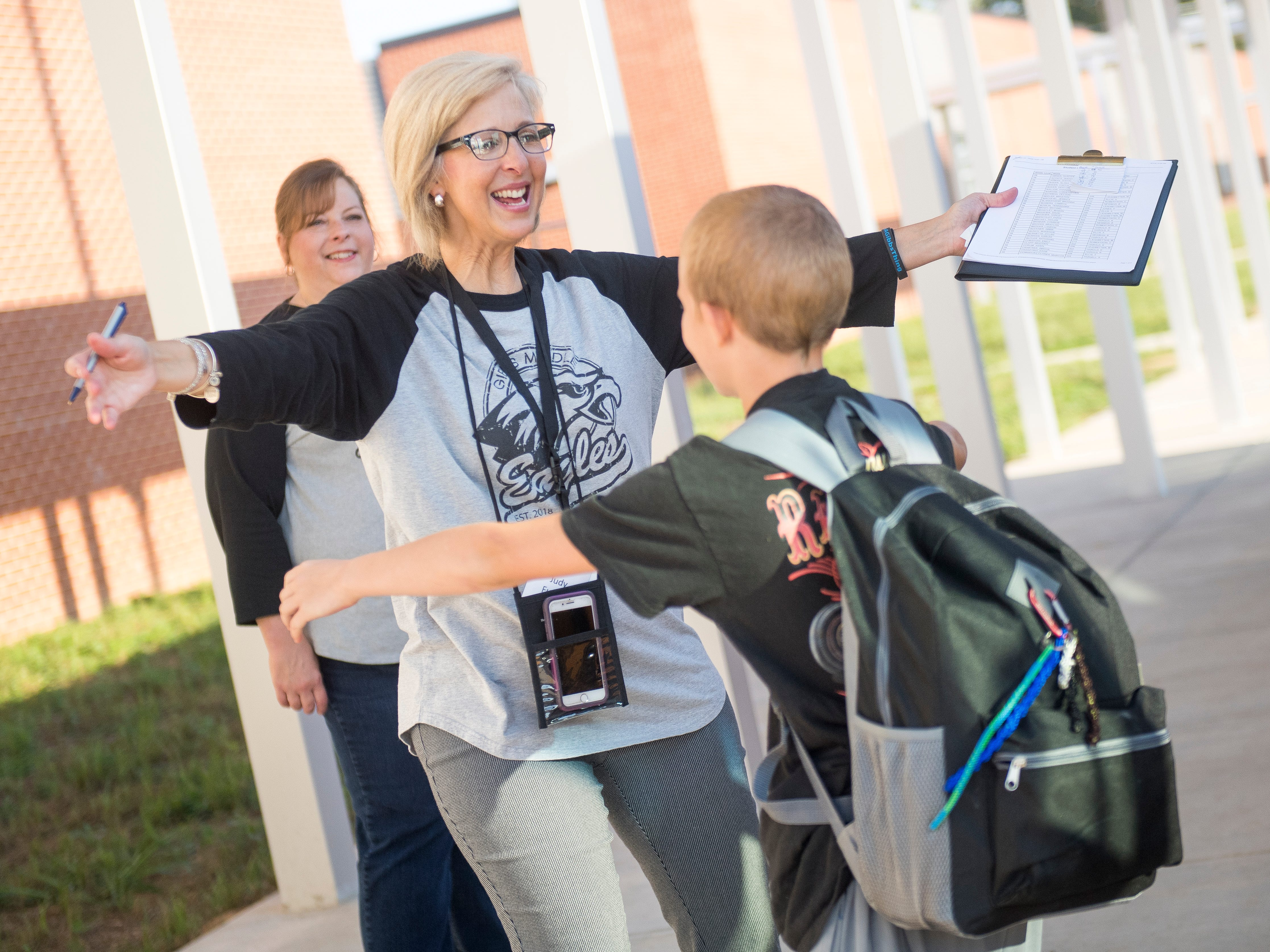 Reading intervention teacher Judy Fugate greets a student with a hug as they enter the new Gibbs Middle School for the first day of school on Wednesday, August 8, 2018.