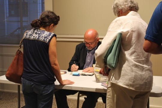 Vince Vawter signs copies of his novels after a discussion Tuesday, August 7 at the East Tennessee History Center.
