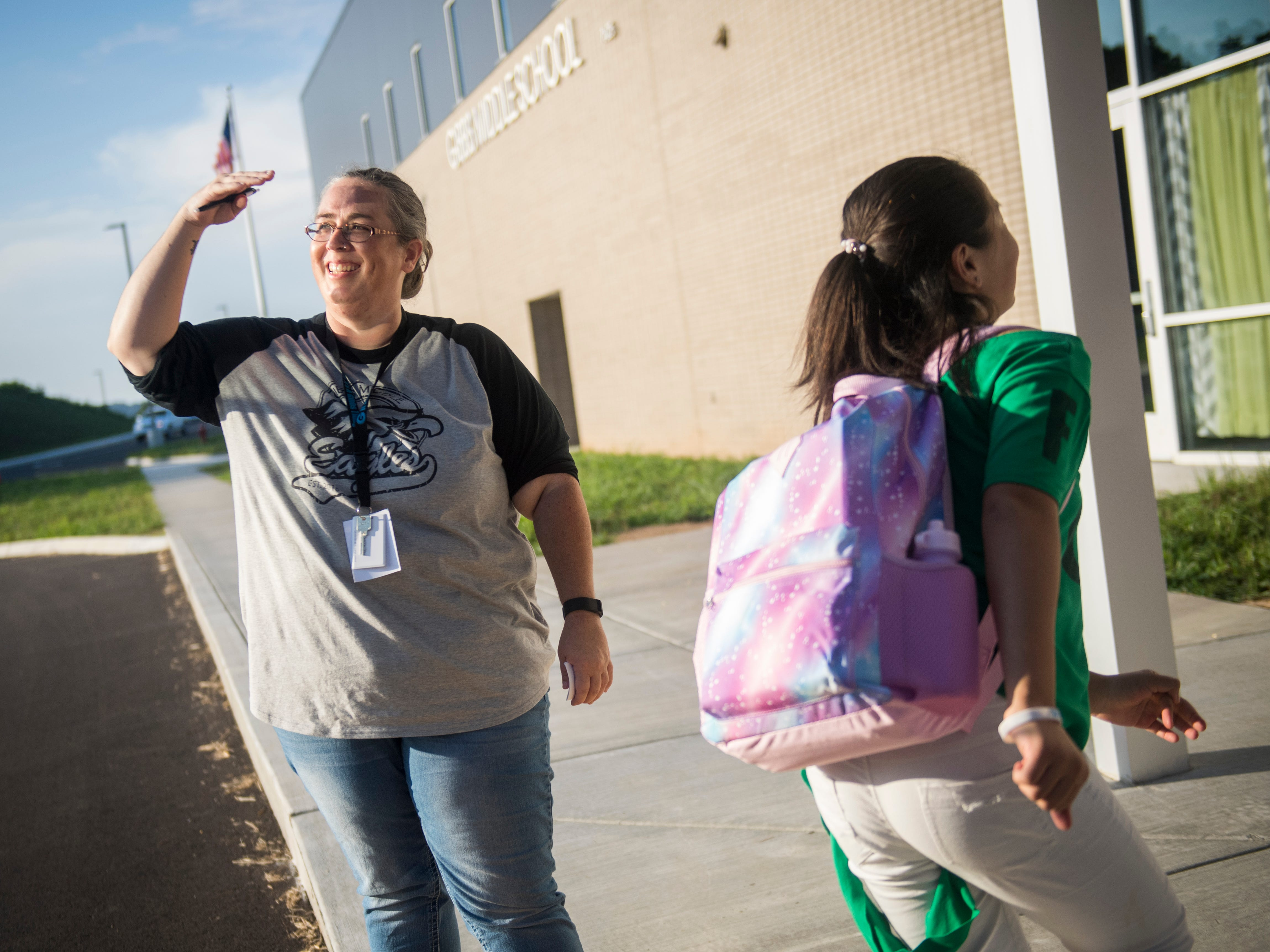 Sixth grade math teacher Jennifer Ewing, left, greets students as they step off the bus and enter the new Gibbs Middle School for the first day of school on Wednesday, August 8, 2018.