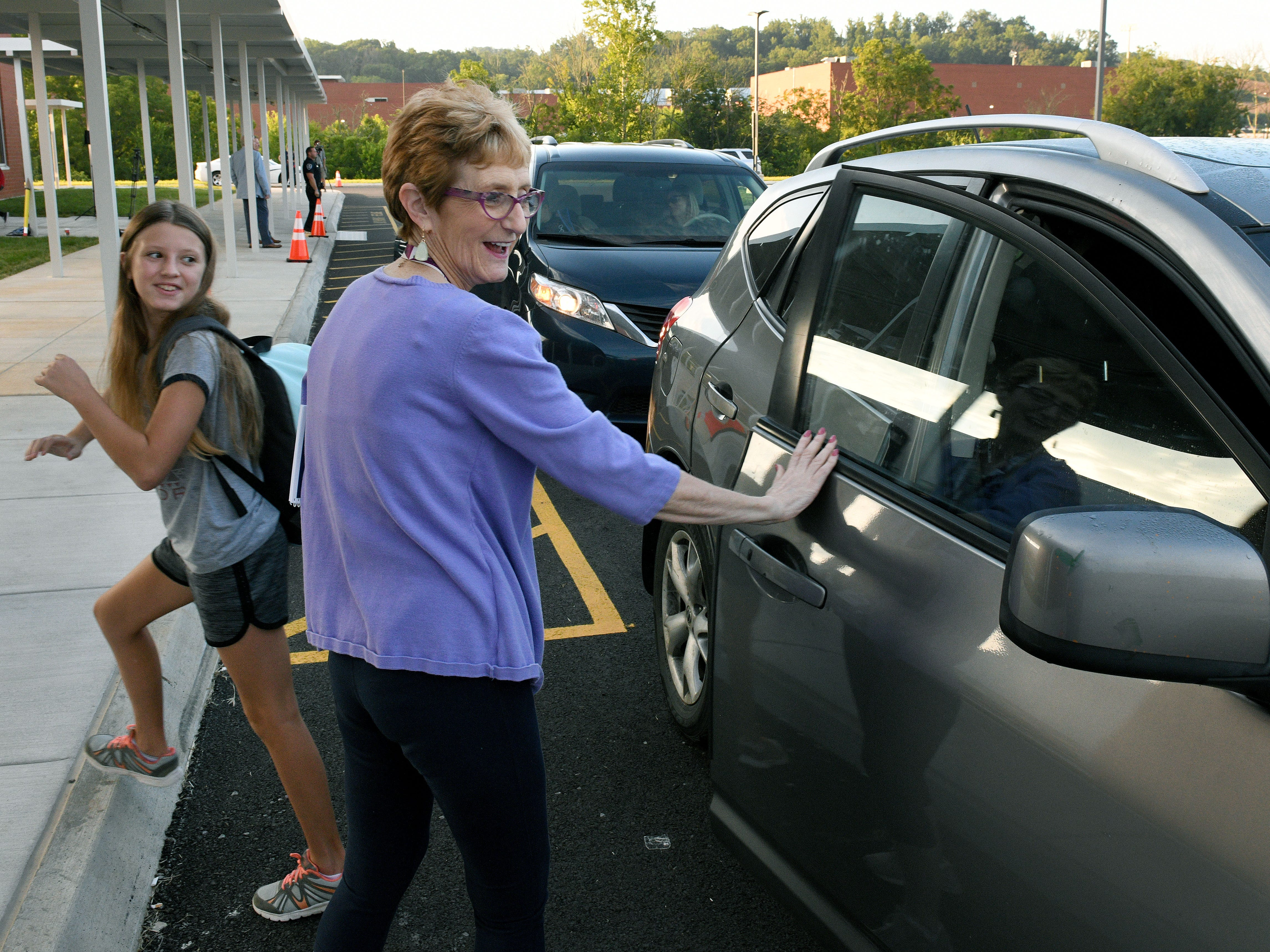Evelyn Stuart greets student car riders for the first day of school at Hardin Valley Middle School Wednesday, August 8, 2018. Principal Cory Smith directed teachers and students to a smooth opening for the new school.
