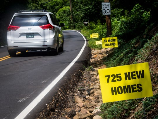 """Signs asking local residents """"Do you want 725 more homes 5x more traffic on this road? Your voice counts Aug. 9 MPC meeting."""" line Tooles Bend Road off Northshore Drive in Knoxville on Wednesday, August 8, 2018."""