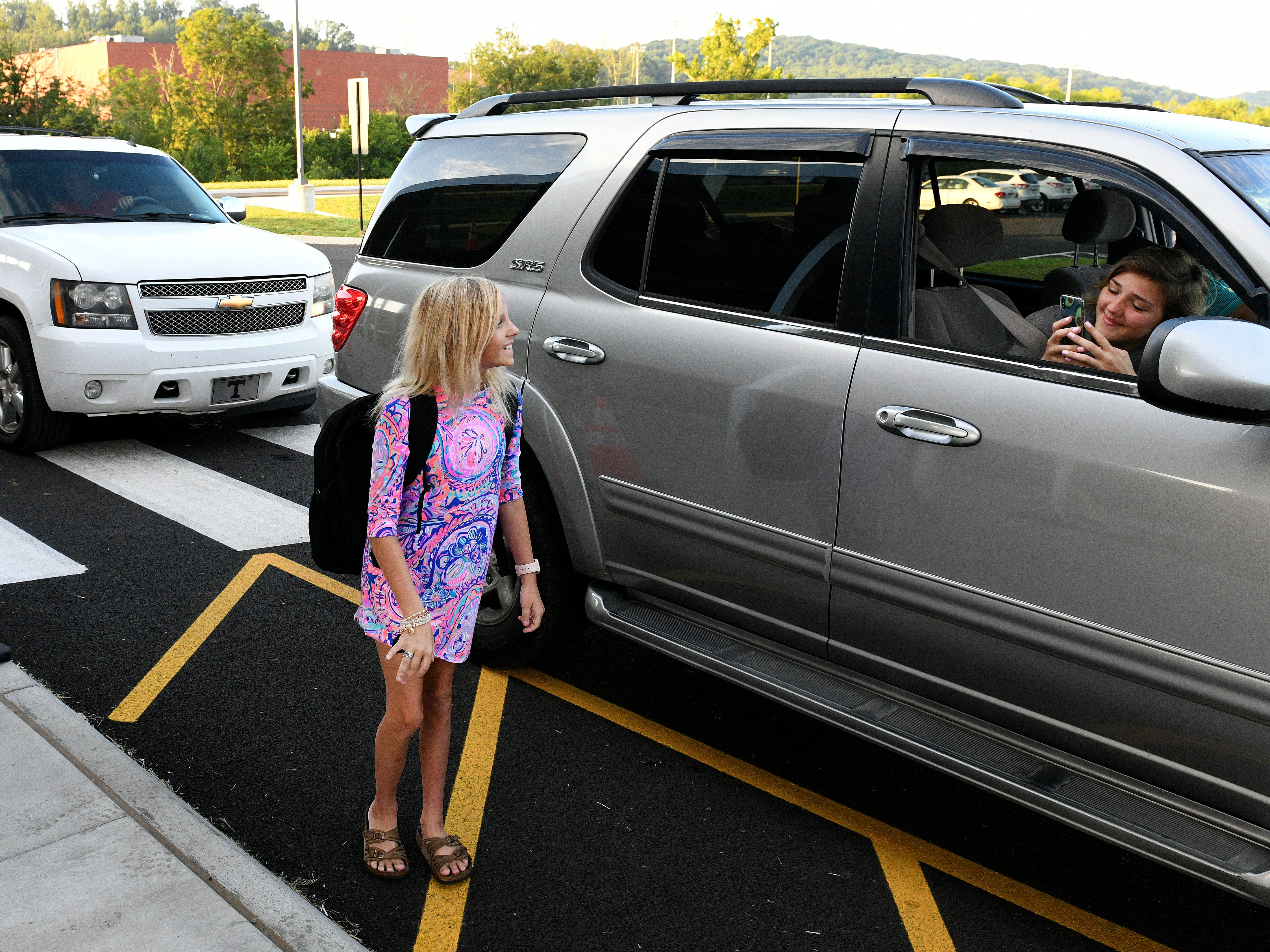 Gracie Mayes, 12, waits for her sister to take a photo as she arrived for the first day at Hardin Valley Middle School Wednesday, August 8, 2018.
