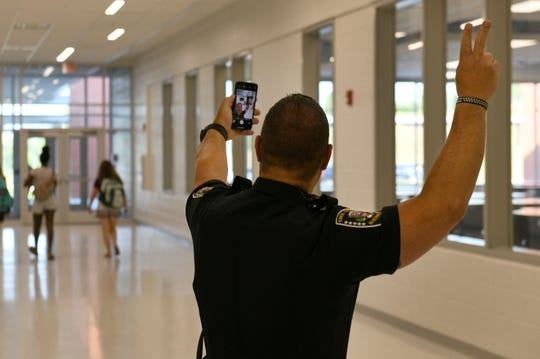 KCSO Officer Brian Dow takes a selfie with teacher in the background during the first morning at Hardin Valley Middle School Wednesday, August 8, 2018.