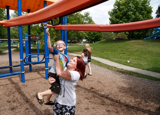 Michelle Berry lifts her son Parker, 5, up to a piece of playground equipment earlier this month in Columbian Park. Berry and her boyfriend share a two-bedroom apartment in West Lafayette with four children.