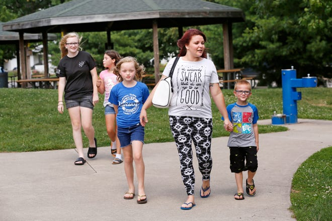 Michelle Berry heads to the playground at Columbian Park with Devon Dillon, 16, from left, Elena Carver, 11, Misty Dillon, 9, and Parker Berry, 5, earlier this month in Lafayette. Berry and her boyfriend and the four children share a two-bedroom apartment in West Lafayette.