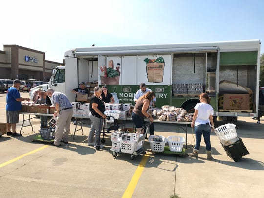 Patrons line up to receive food items from the Food Finders Food Bank mobile pantry August 2 at 823 Park East Boulevard in Lafayette.