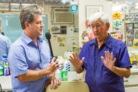 Grammy-winning musician Steve Riley visits with old-school barber Grant Clement who has been cutting hair for 60 years. Wednesday, Aug. 1, 2018.