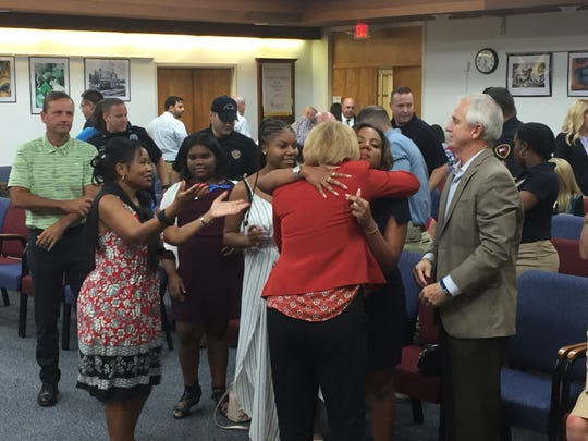Lafayette Parish School Board members Mary Morrison and Dawn Morris hug the family of Cpl. Michael Middlebrook at the Aug. 8, 2018 board meeting.
