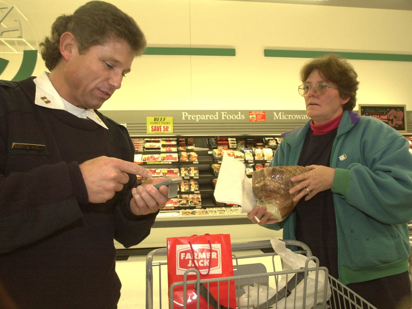 Delta Fire Captain Duane Haring adds the price of a ham to his grocery total as he and Linda Davis shop for St. Vincent Home for Children, Oct. 16, 2001, at the new Farmer Jack in Delta Township.  This was a charity shopping spree in which shopper for local charities were given fifteen minutes to load up there carts with food up to $600.