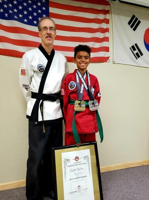 Lakeshore Tae Kwon Do's Julien Bailey (right), 10, won the national championship for patterns for his age and rank and took second in sparring at the 11th annual United Tae Kwon Do Alliance Grand National Championship in late July in Shreveport, Louisiana. The school's owner, Mark Weber (left), was named Master Instructor of the Year at the event.