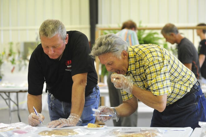 Charles Pierce samples a pie as Rick Evans writes his judge's remarks during the pie contest Wednesday at the 2018 Richland County Fair.
