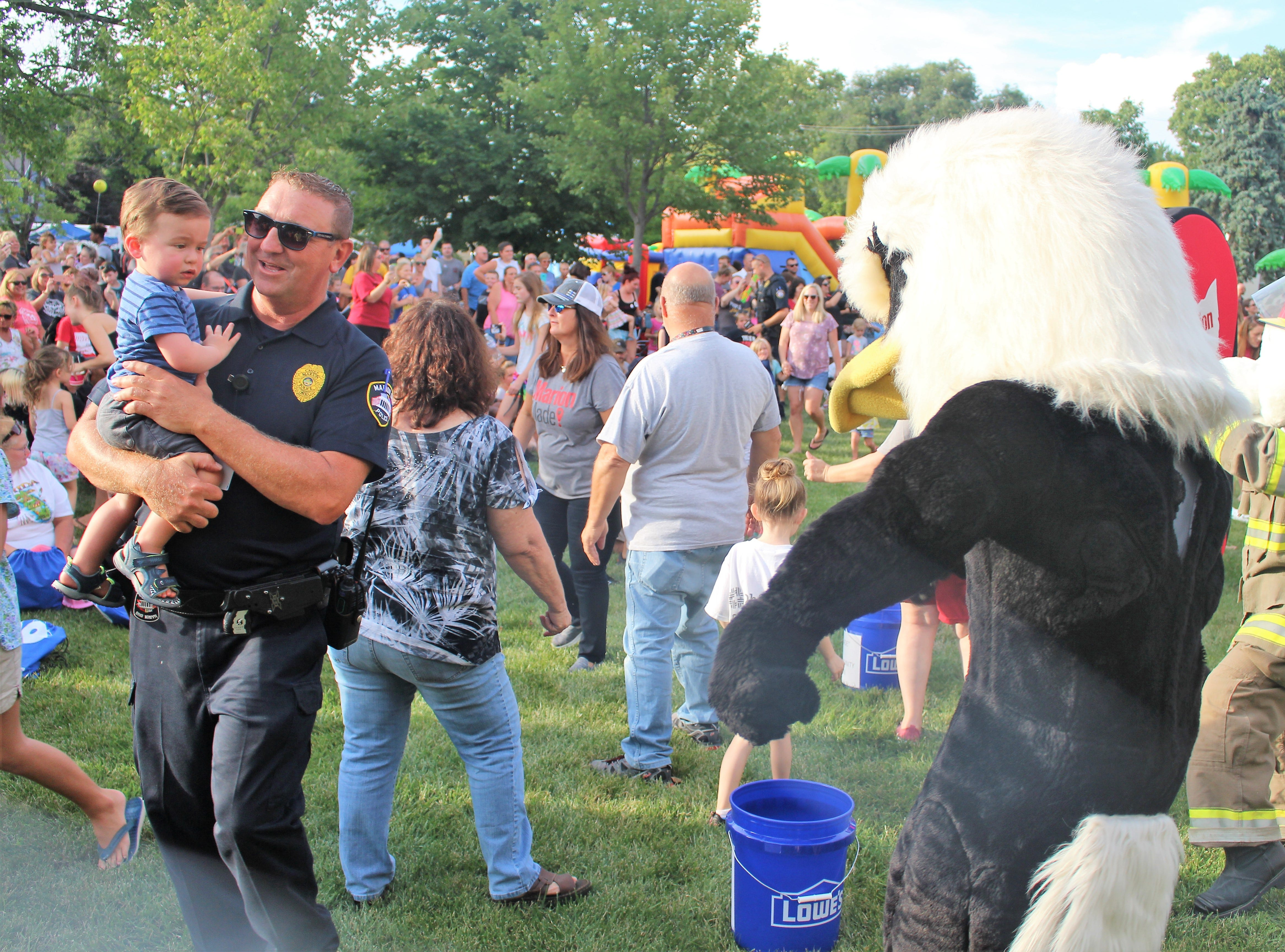 Marion Police Chief Bill Collins walks by the mascot for Marion City Schools during a National Night Out event at Grant Middle School Tuesday evening. The event aims to build up relationships between local police departments across the country and the communities they serve.