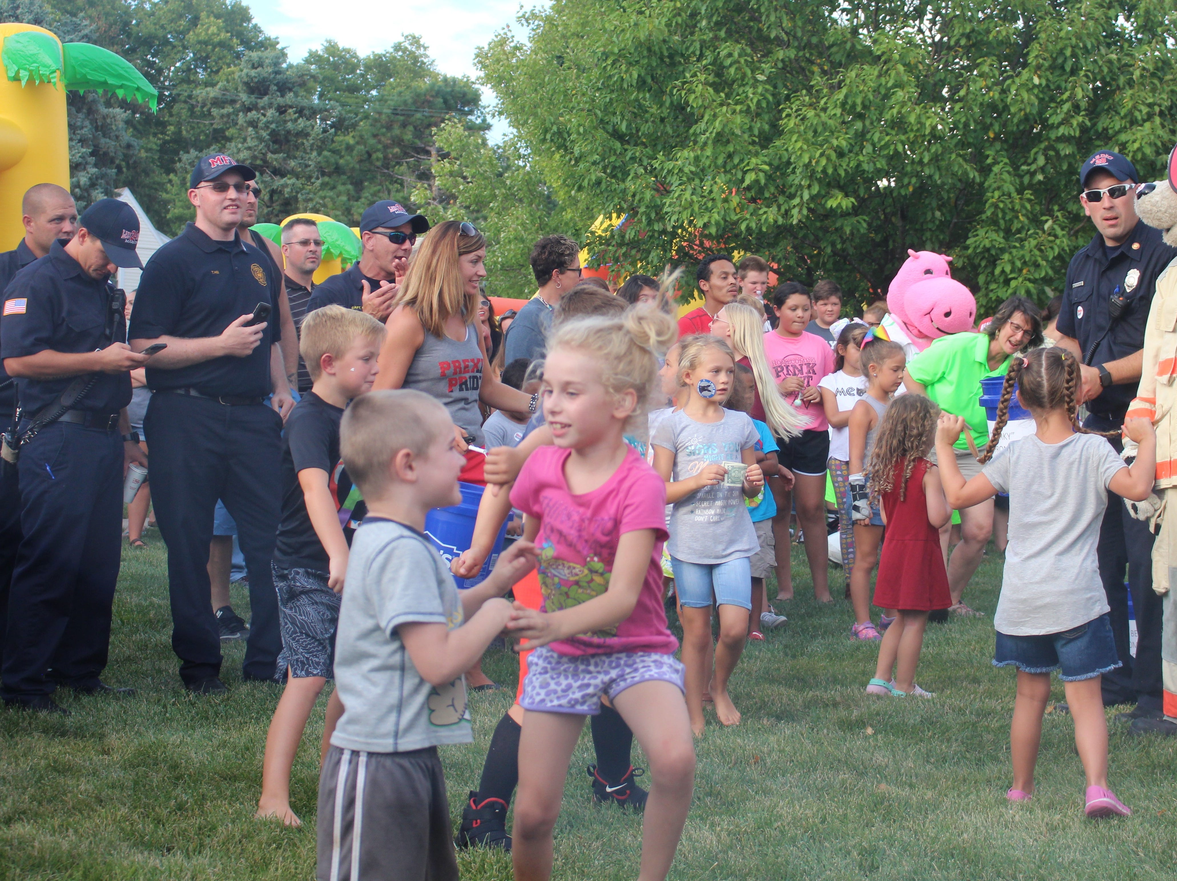 Marion City Firefighters watch as their mascot dances during a competition to see who could raise the most donations during the National Night Out event at Grant Middle School on Tuesday.  Attendees were asked to place donations in buckets placed in front of the mascots. The donations will go towards the event next year.