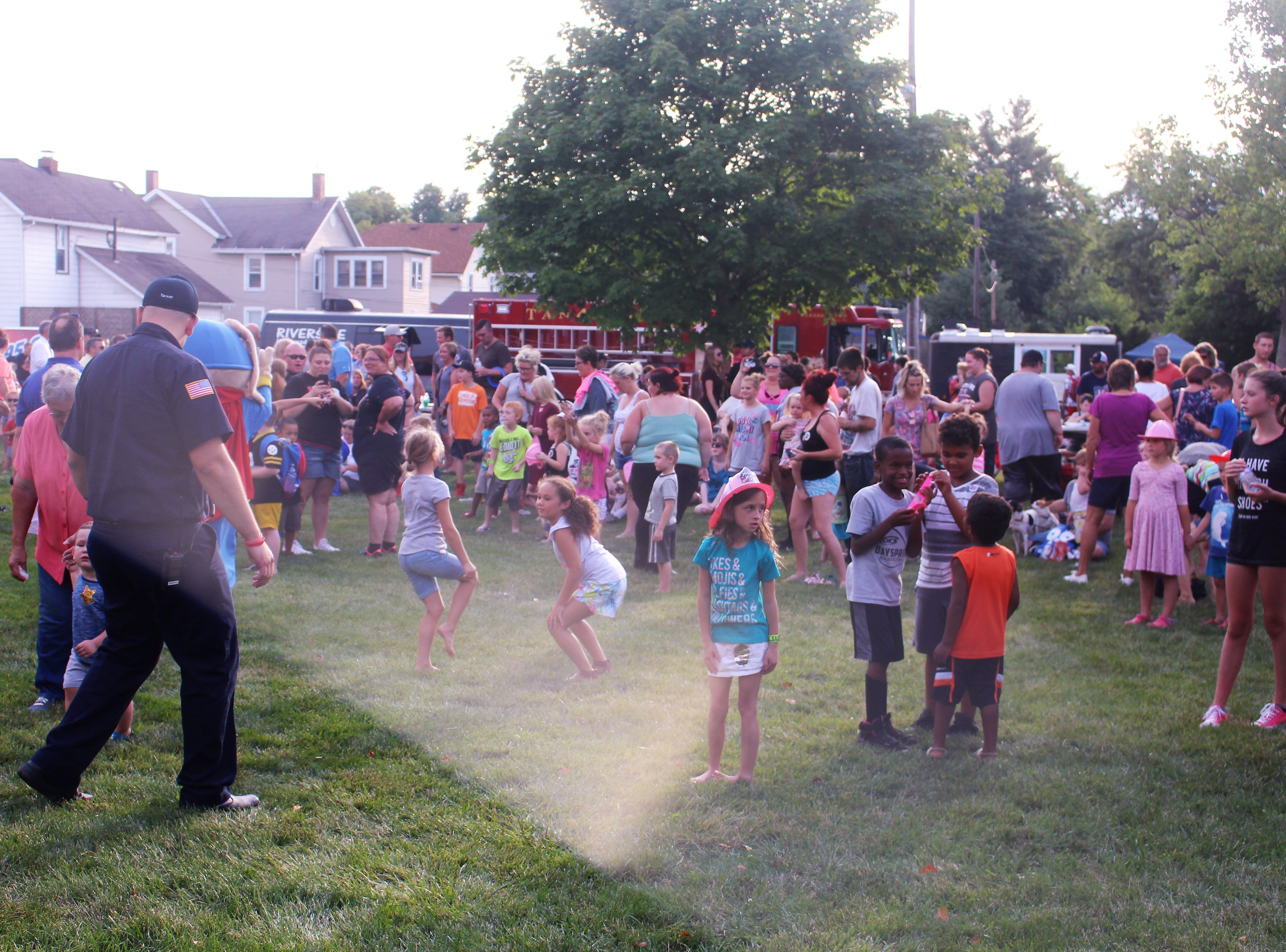 Children dance under the watchful eye of their parents during the National Night Out event outside Grant Middle School on Tuesday.