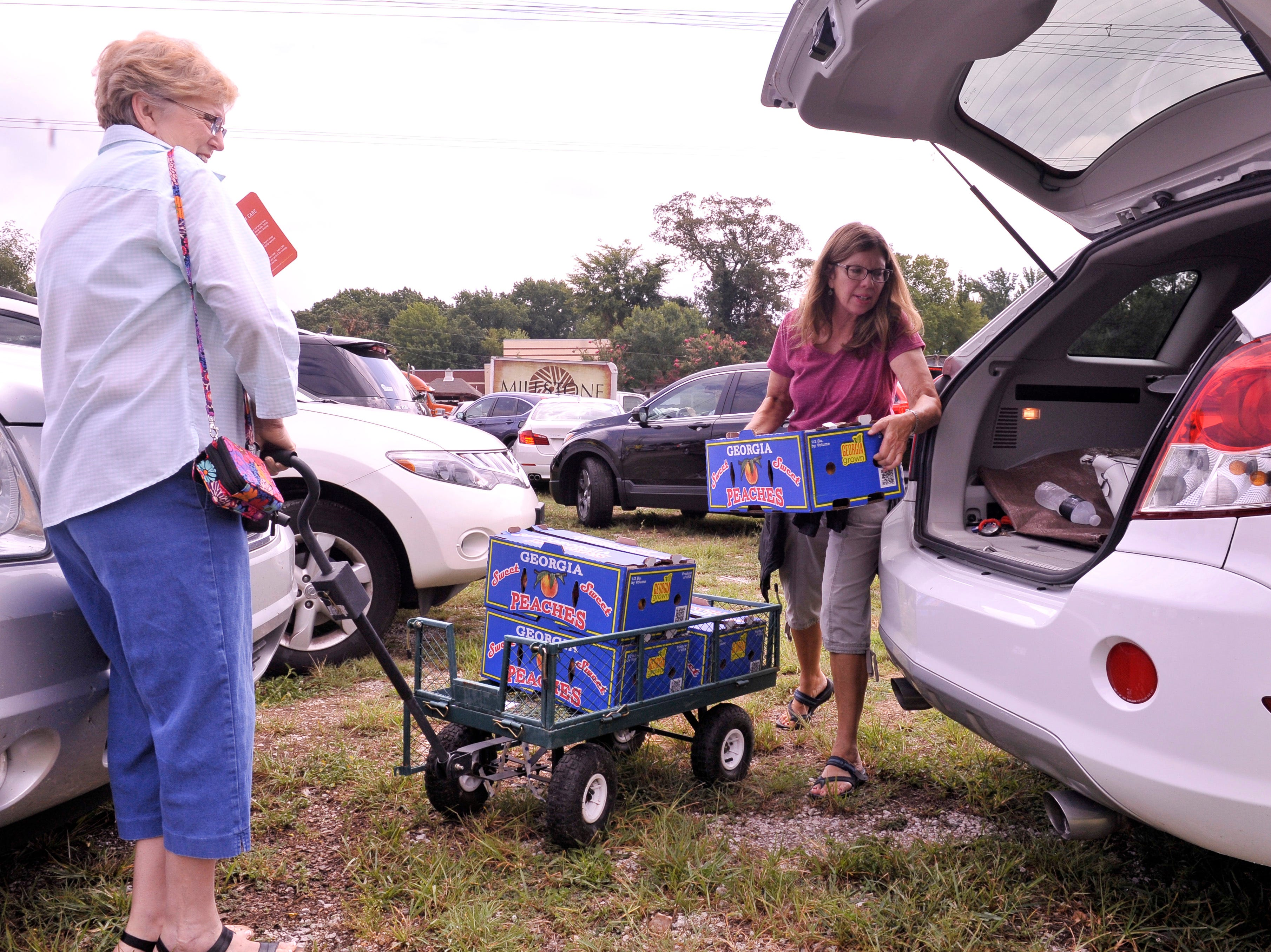 Judy Hill to the right watches as Cindy Matz loads peach's into her car after visiting The Peach Truck, which made a stop at Millstone Nursery on Popular Avenue on Wednesday.