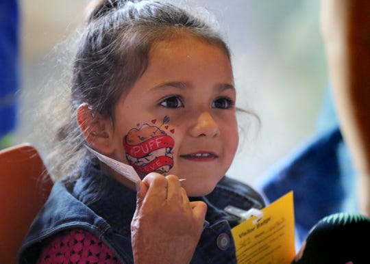 Mia Camarillo, 7, remove the paper backing from a temporary tatoo applied to her face during State Fair at Children's Hospital on Aug. 7.