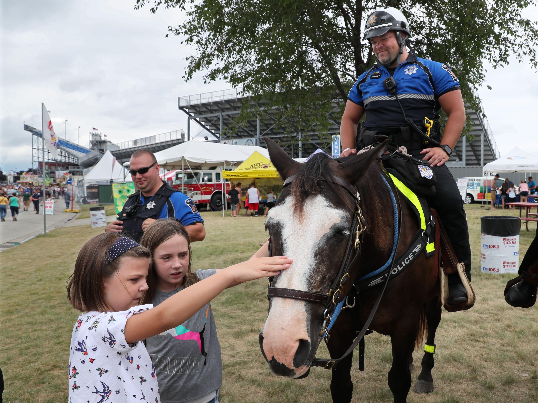 Jana Kotrly, left, and her sister, Audrey Kotrly, both of Brookfield, pet officer Nathan Anhalt's horse Lil Joe.