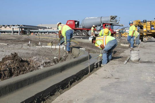 Workers pour cement for the parking lot expansion portion of projects at Hamilton High School. Specfically, the cement for the curbs that they are installing.
