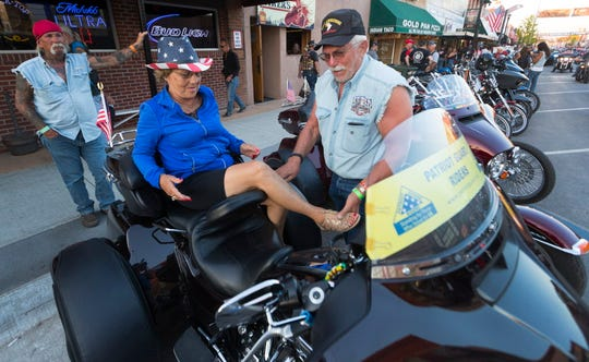 Don Pratt of Kansas City, Mo., helps his wife, Jackey, off of their Harley-Davdison trike in Sturgis, S.D.