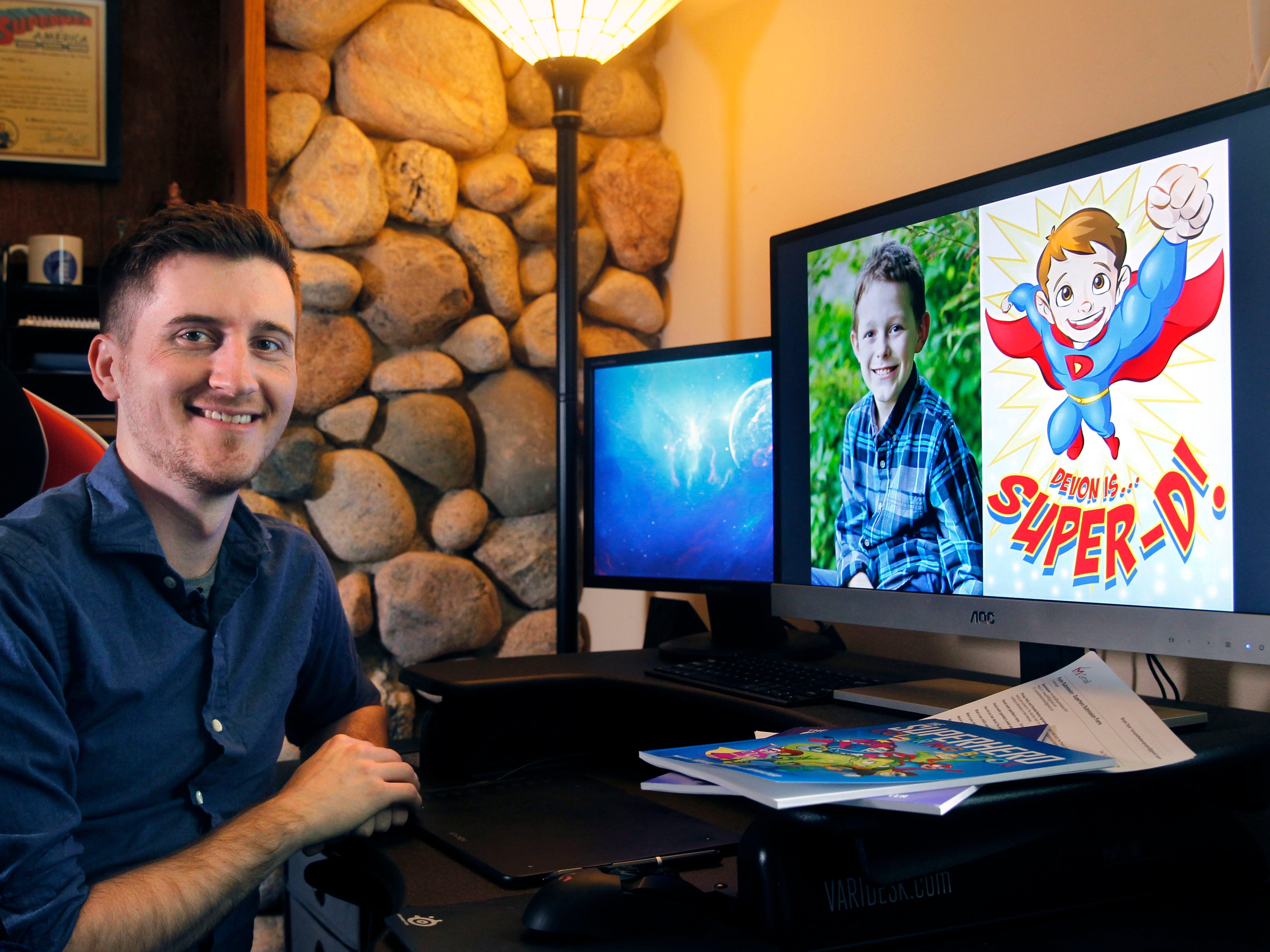 Bryan Dyer, owner of You Are the Hero,  is an illustrator for kids with chronic or critical conditions. On the monitor is Devon Sweeney, one of his superhero creations seen on Aug. 3, 2018, Germantown.
