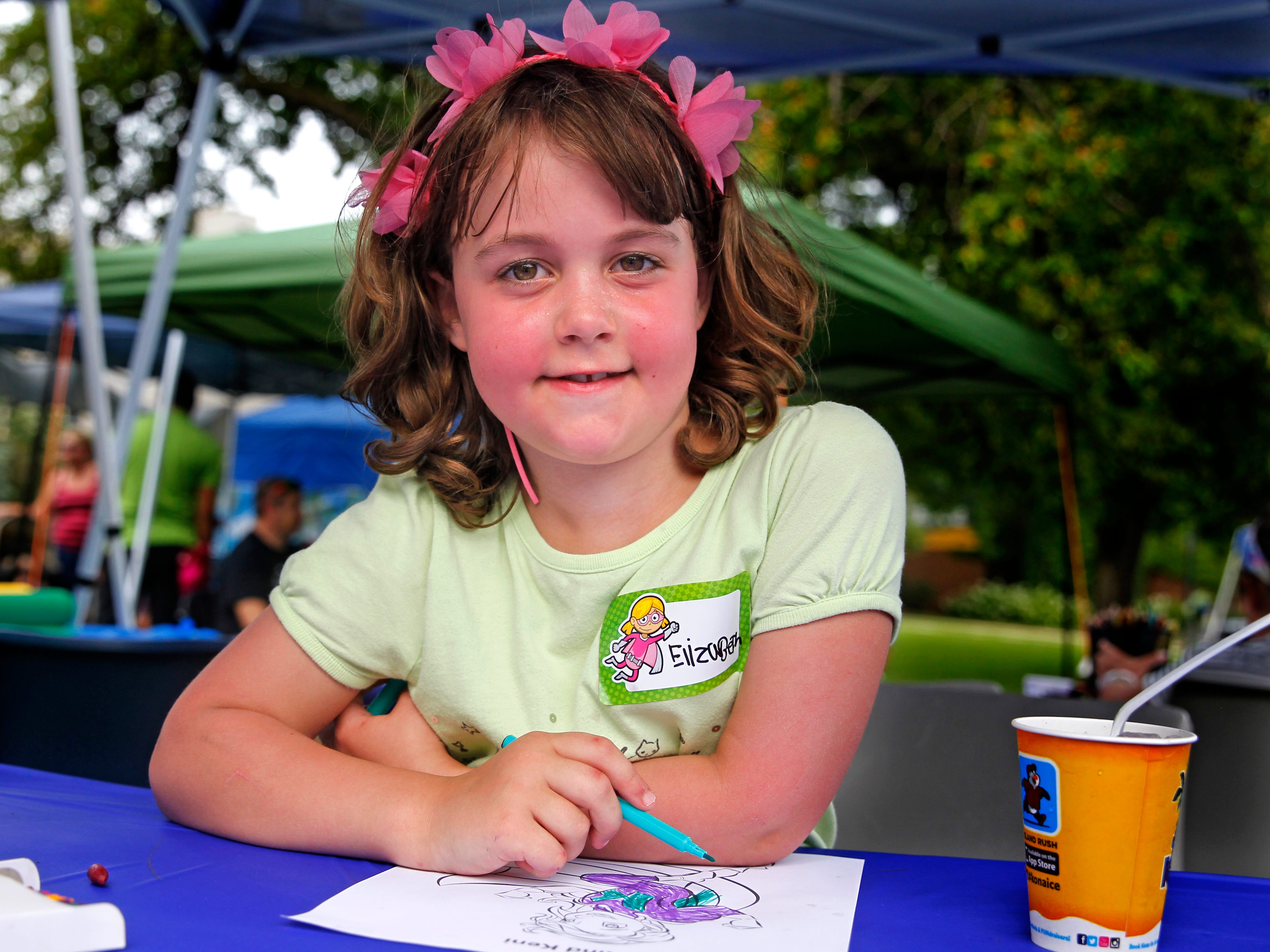 Elizabeth Handrick, 7, of Wauwatosa, pauses for a photo while coloring one of the superheros created by Bryan Dyer, owner of You Are the Hero and an illustrator for kids with chronic or critical conditions on August 4, 2018, the Gamerosity's GameOn at Marquette University. Elizabeth was 4 years old when she was diagnosed with leukemia. Her mother, Martha, said as part of her healing after her treatment she wanted to celebrate with having Dyer create a superhero for her. Elizabeth met Dyer for the first time at the GameOn event.  The event brings awareness to children and families affected by childhood cancers.