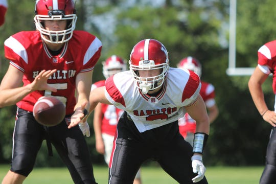 Hamilton running back Jackson Kollath prepares to take a hand-off from quarterback Eric Erato during practice on August 8.