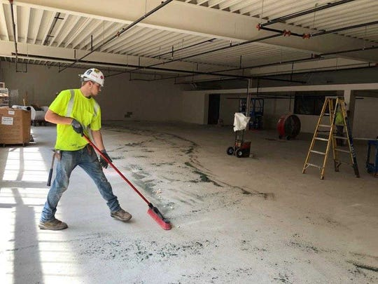 A construction worker cleans the floor of the woods lab ahead of concrete staining work to be done.