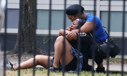 In this Sunday, Aug. 5, 2018 photo, two women cry outside the Stroger Hospital in Chicago, after they were asked to leave due to overwhelming crowds of family and friends of shooting victims.