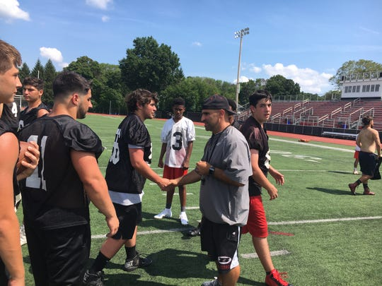 Boonton head football coach Bryan Gallagher shakes each of his players' hands as they head off the field Wednesday.