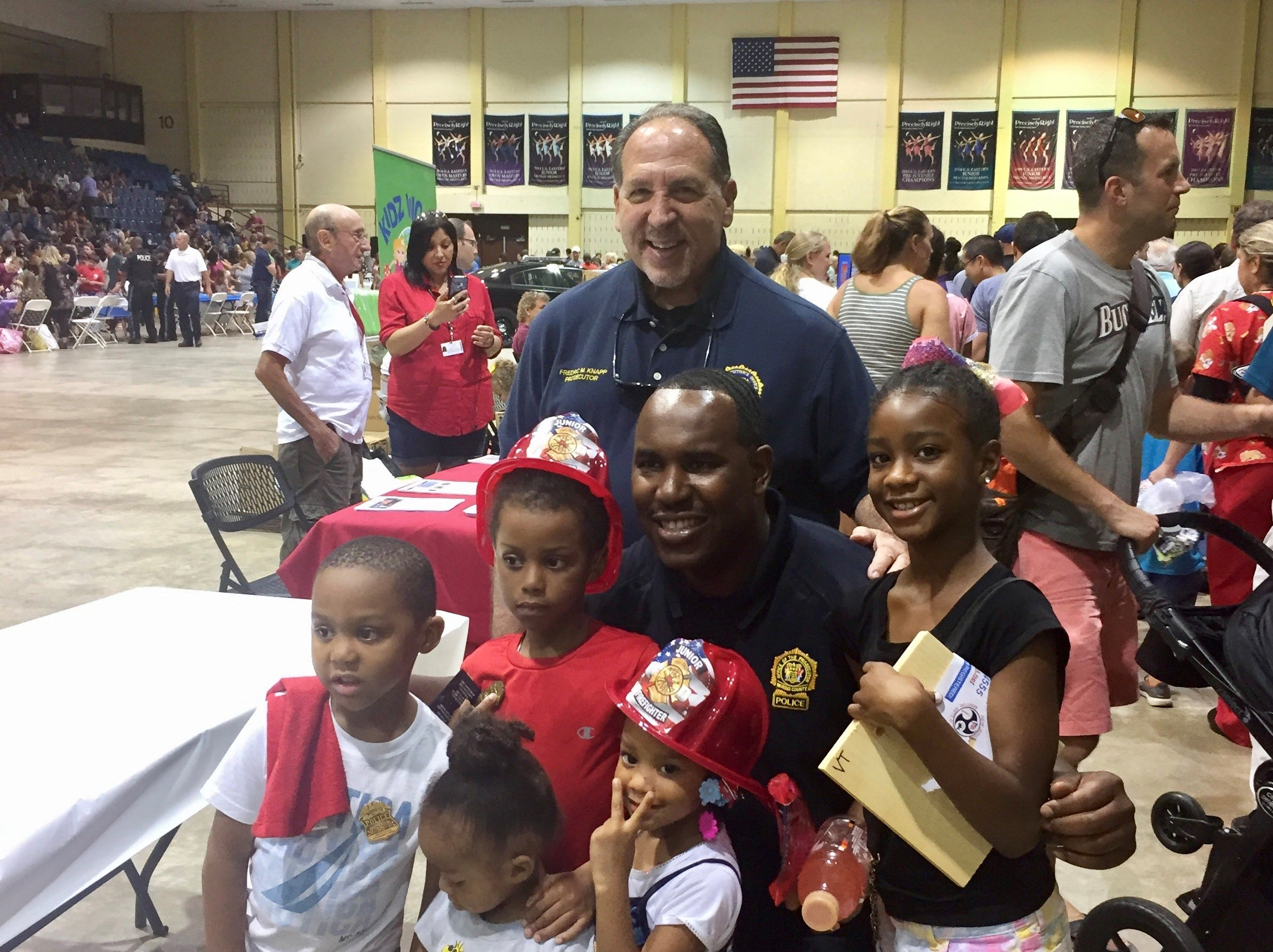 Prosecutor Fredric M. Knapp and Det. Sup. Patrick LaGuerre with youngsters at the National Night Out event at Mennen Arena on Tuesday, August 7, 2018.
