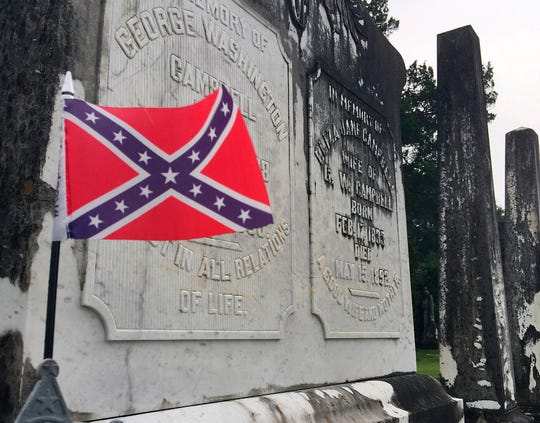 ADVANCE FOR THURSDAY AUG. 9, 2018--A small Confederate battle flag waves at the grave of a Confederate veteran in a cemetery in Tuskegee, Ala., on Tuesday, July 31, 2018. The mostly black city still has a Confederate monument dedicated in 1909 by the United Daughters of the Confederacy, which has a small chapter in the city. (AP Photo/Jay Reeves)