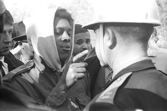 ADVANCE FOR THURSDAY AUG. 9, 2018--This photo provided by Alabama Department of Archives and History, from January 1966 shows Simuel Schutz Jr. speaking to a police officer during a protest following the shooting of a black man by a white man in Tuskegee, Ala. Schutz, who was active in the civil rights movement, says he was part of a group that later tried to topple a Confederate monument at the center of the mostly black city. (James Peppler/Alabama Department of Archives and History via AP)