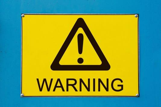 Warning Sign On Yellow Metallic Board