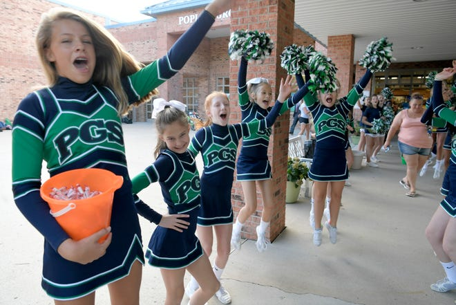 Poplar Grove School cheerleaders welcome back students with cheers and candy on the first day of school in Franklin on August 8, 2018.
