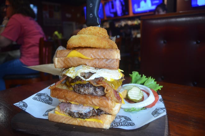 The Chubby has two half-pound patties with smoked brisket, hickory-smoked bacon and smoked ham between three grilled cheese sandwiches and finished with fried onion rings and an over easy egg.