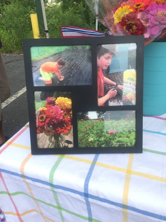 As part of his tent display at the Tuesday Granville Farmers Market, Eli Davidoff includes images of himself planting his zinnias.