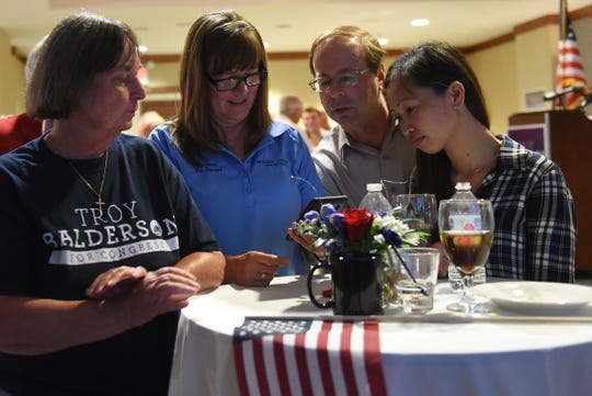 Troy Balderson supporter Pat Davies (center) refreshes results as Dixie Shinaberry, Todd Emoff and Lhynne Tuzon watch early election results coming in showing the Republican candidate Balderson ahead of Democratic candidate Danny O'Connor. Tuesday night's special election for Ohio's 12th congressional district was a tight race with Balderson leading O'Connor 50.2 percent to 49.3 percent, a margin of just 1,754 votes.