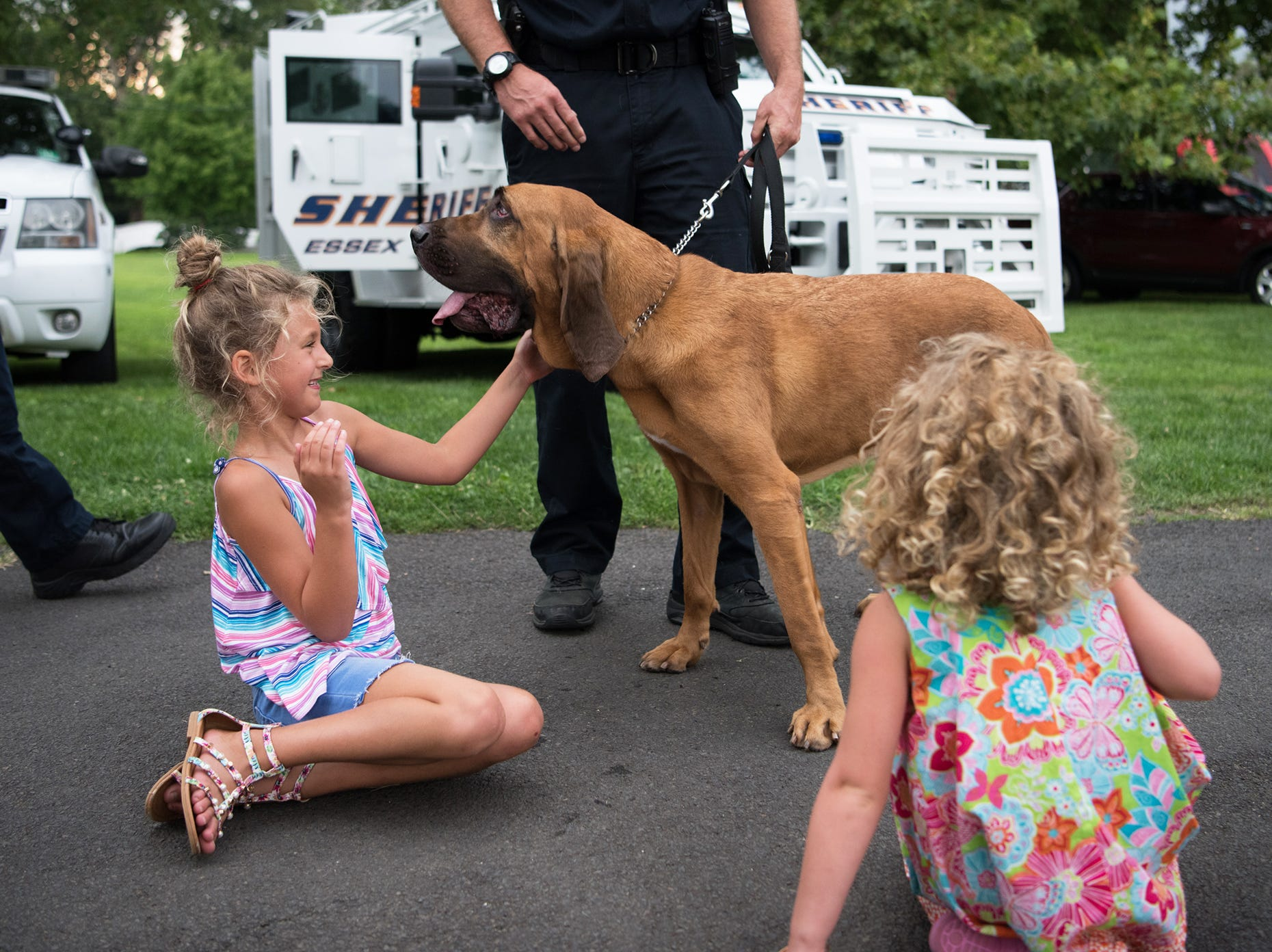 A bloodhound dog named Joe is handled by Detective Tesei and is being pet by Carolina and Laurel Brown at the National Night Out in Millburn, NJ. Tuesday, August 7, 2018.