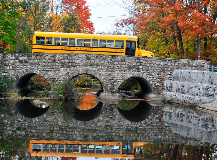 The Lake Shawnee Road Bridge has a rustic charm all its own, but add a touch of fall color and the view becomes priceless. An equally bright Jefferson Township school bus crosses over the bridge in October 2014 as it leaves neighborhood Stanlick School.