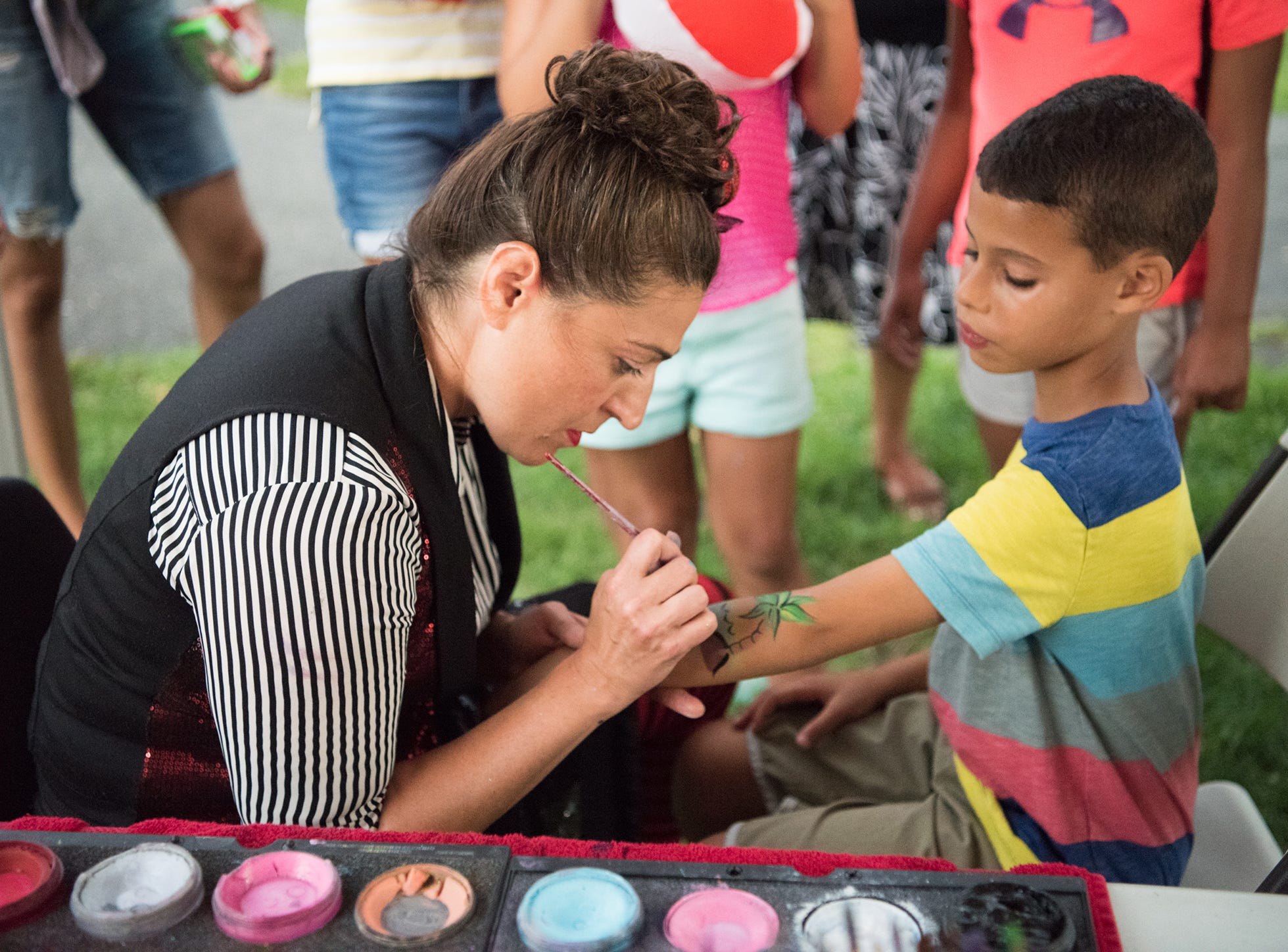 Mason Murphy gets a palm tree painted on his arm at Millburn's National Night Out at Taylor Park. Tuesday, August 7, 2018.
