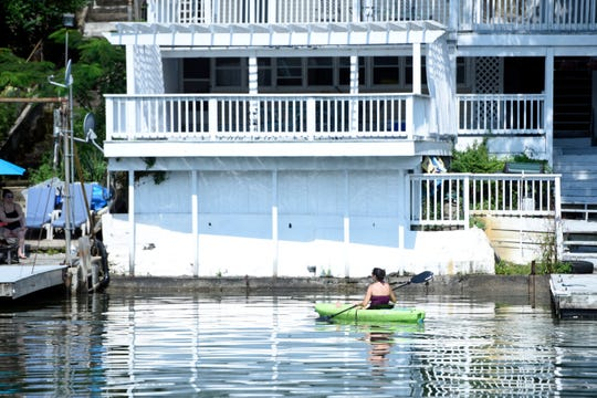 A woman kayaks in front of a home on Greenwood Lake on Wednesday, August 8, 2018.