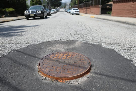 A manhole cover is shown on Danforth Ave. in Paterson. Mayor Andre Sayegh  said many congregation members at St. Bonaventure Church specifically asked for Danforth to be repaved.