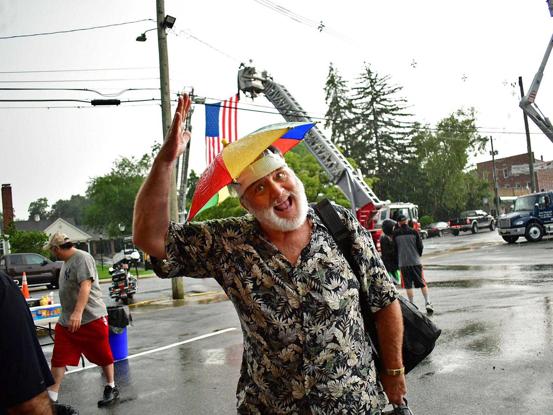 Tim Wendt heads into the garage during a downpour of rain.  Butler Police Station hosts National Night Out.  Heavy rain hit and then a rainbow appeared after it, over the station.  In Butler on Tuesday eveningl August 07, 2018.